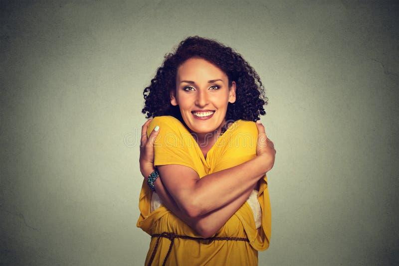 Tenuta sorridente felice della donna che si abbraccia immagine stock