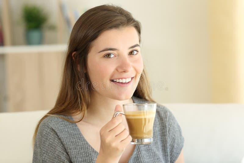 Tenuta teenager felice un caffè con latte che vi esamina fotografia stock