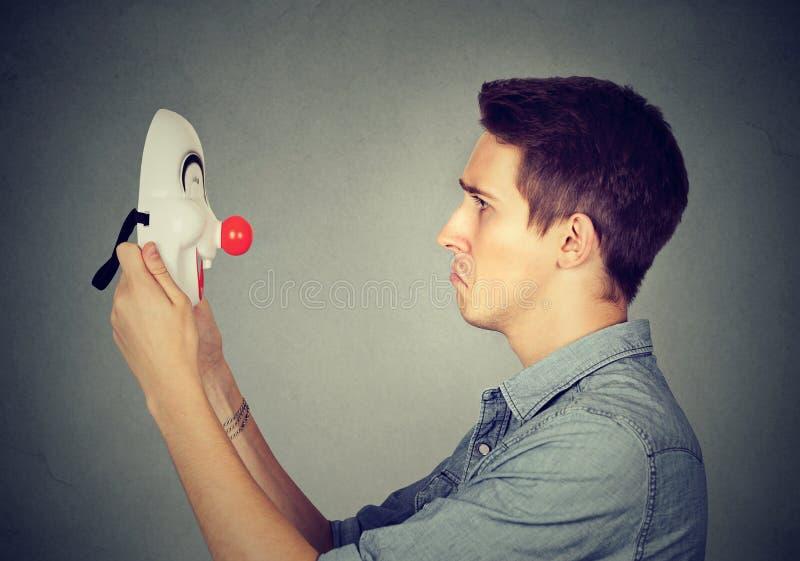 Tenuta triste dell'uomo che esamina la maschera felice del pagliaccio fotografia stock