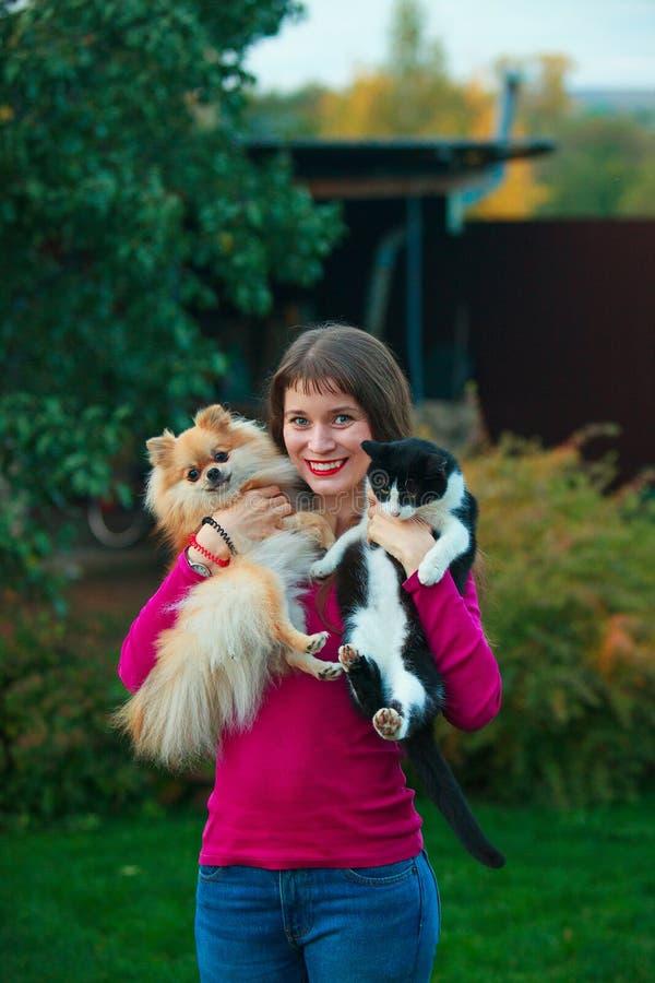 Tenute della donna sulle mani gatto e cane fotografia stock libera da diritti