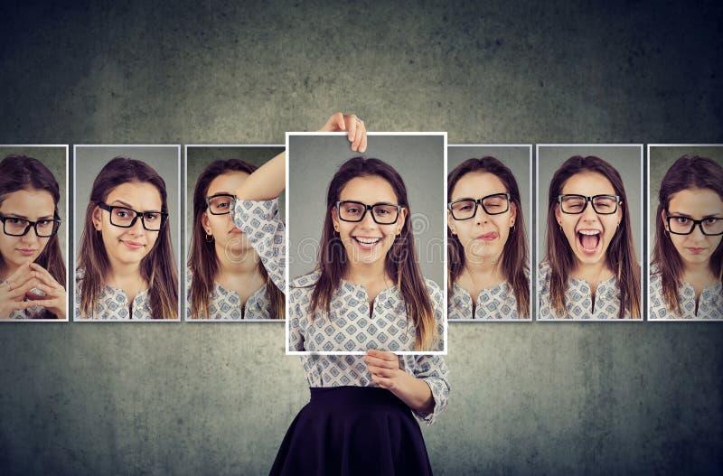 Tenute della ragazza e cambiare i suoi ritratti del fronte con differenti espressioni fotografie stock