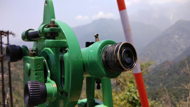 Teodolito verde en el terreno montañoso imagenes de archivo