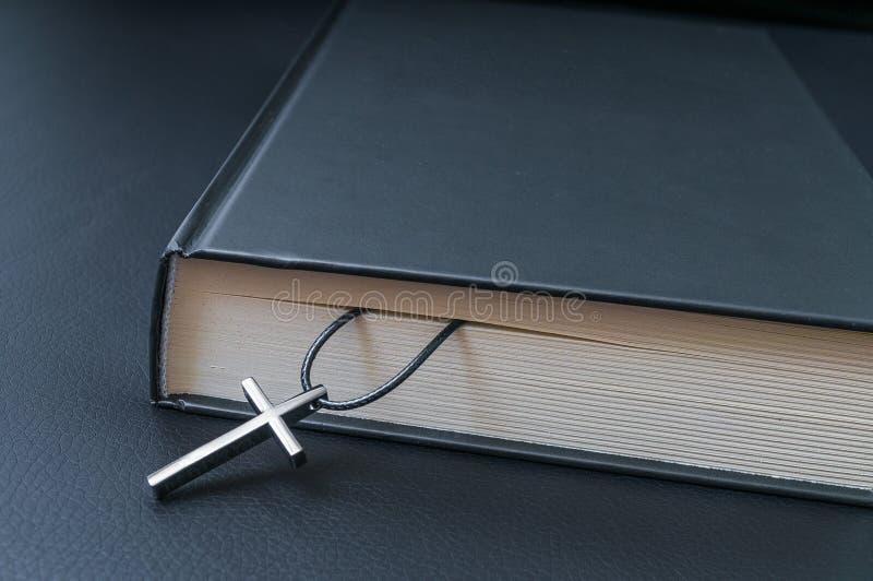 Teologibegrepp Metalliskt kors och helig bibel på svart backgro royaltyfri fotografi