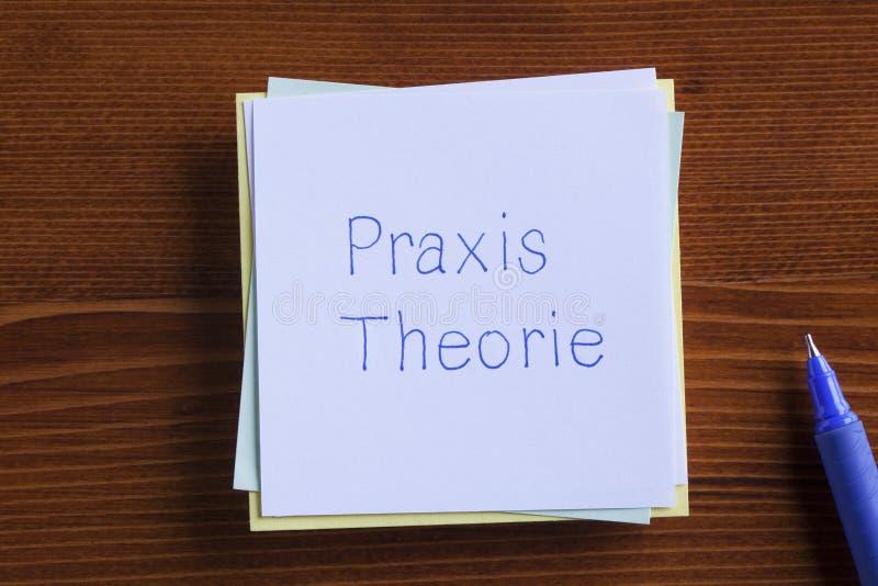 Teoría y práctica en alemán escrita en una nota imagen de archivo