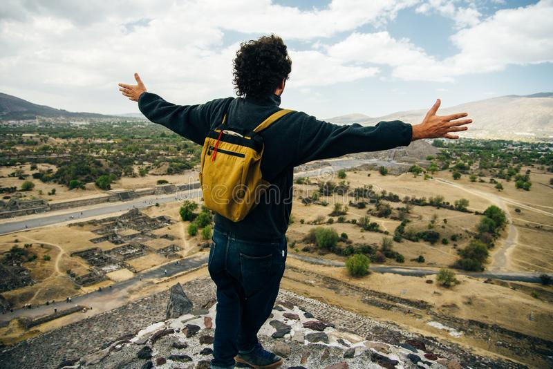 Teotihuacan, Mexico. A Mexican American tourist with a backpack and hat enjoys the view from the top of the Pyramid. The Sun stock photos