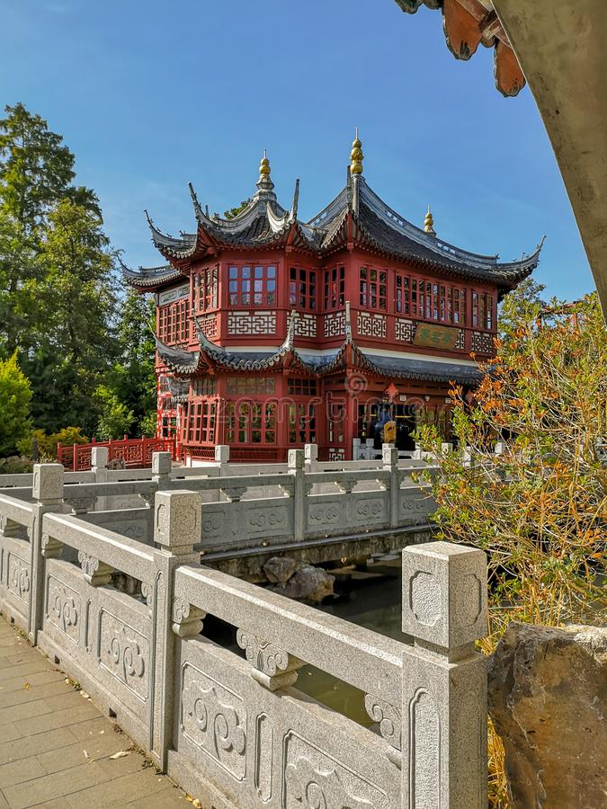 Tepaviljongen i traditionell röd färg med blåa takstrålar i den kinesiska trädgården i djurlivet parkerar Pairi Daiza royaltyfria foton