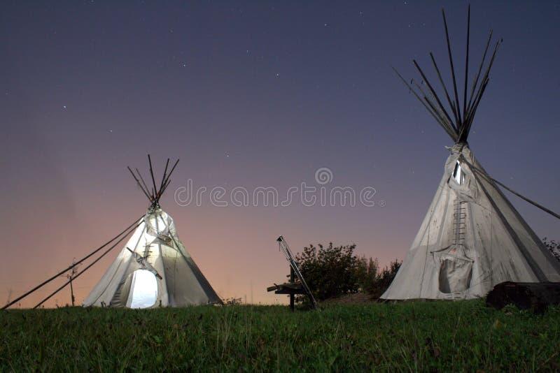 Tepees (Tipis) na noite fotos de stock