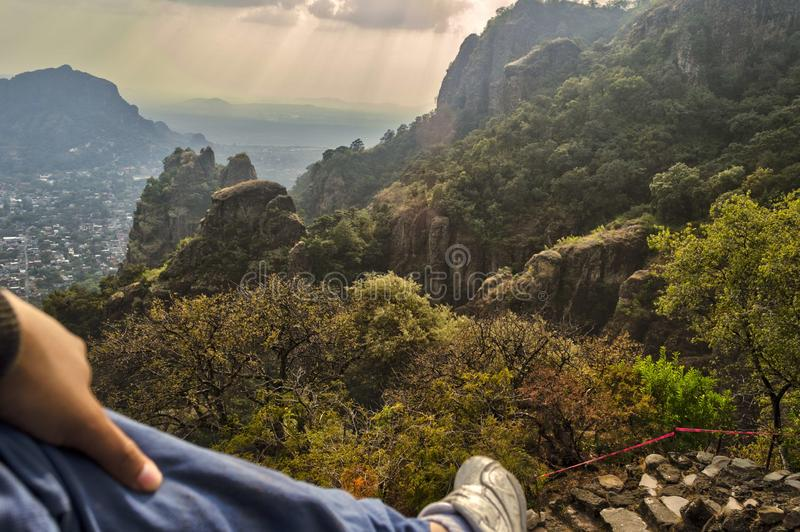 Foot of man contemplating the horizon at the top of Tepozteco Hill in Tepoztlan. Beautiful mountainous view. stock images
