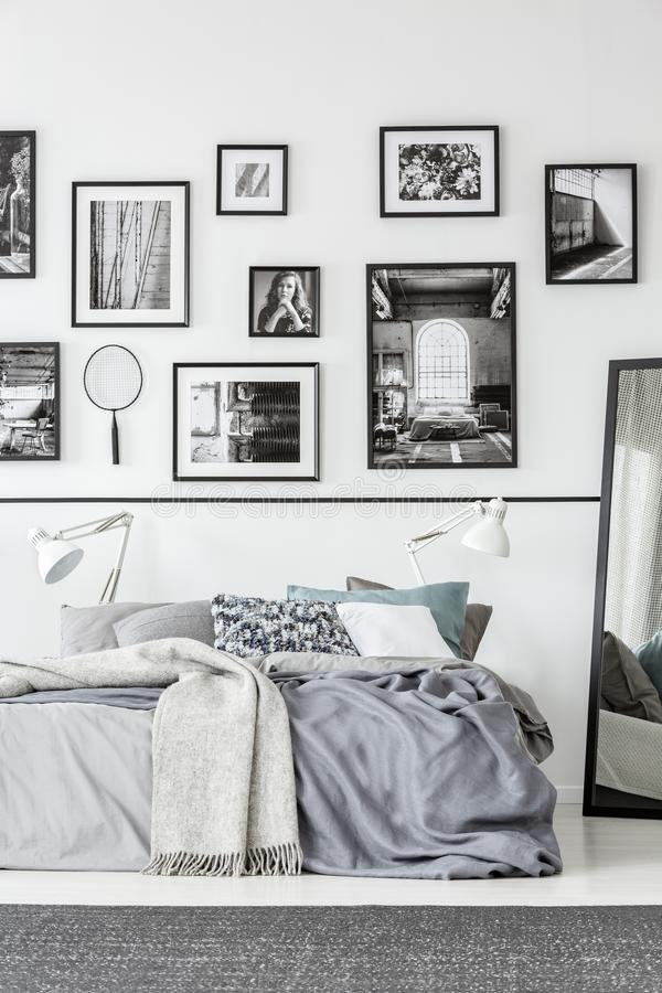 Teppich vor Bett und Spiegel im weißen und schwarzen Schlafzimmerinnenraum mit Galerie Reales Foto lizenzfreies stockfoto