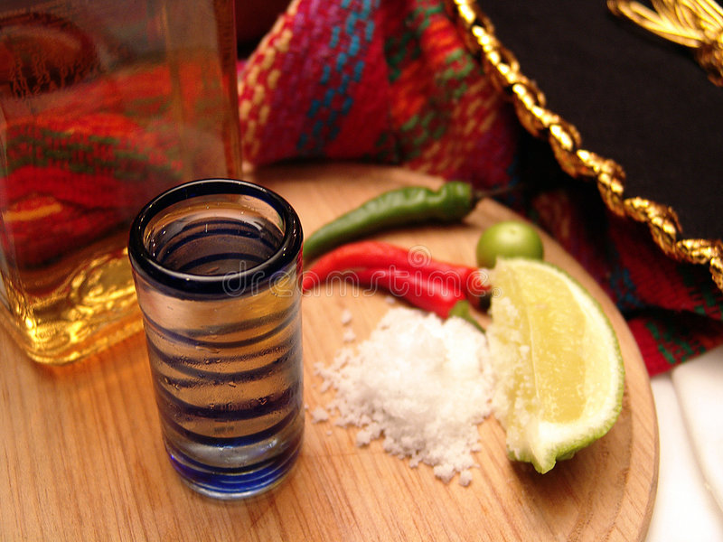 Tequila. Bottle and glass and lemon slices on a wood plate royalty free stock photography