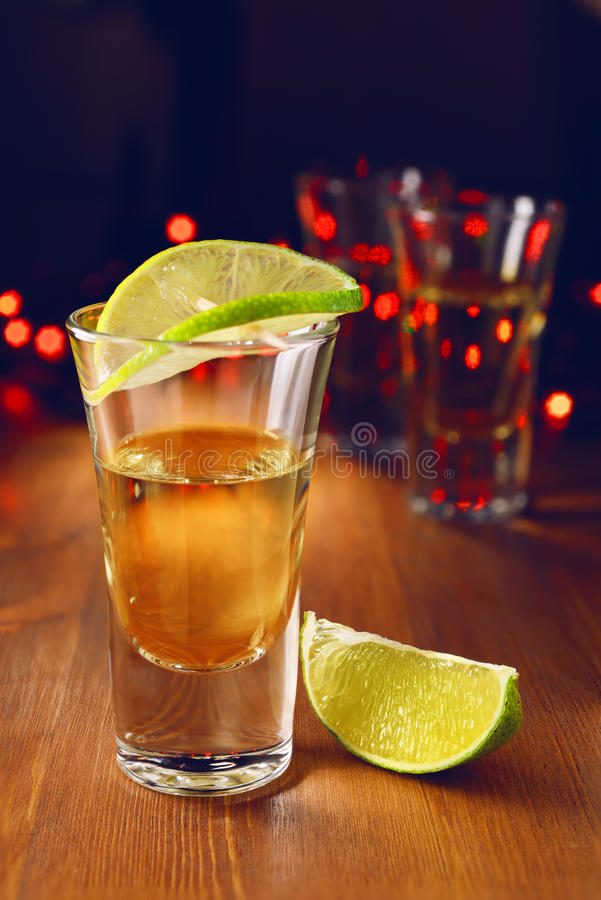 Tequila on bar counter. Gold tequila shot with lime on the wood bar counter stock photo