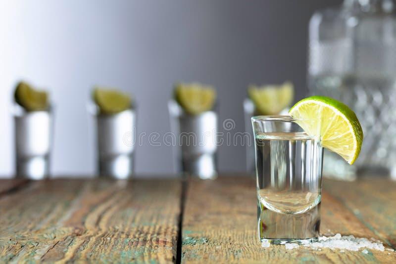 Tequila con la sal y la cal en un viejo fondo de madera imagenes de archivo