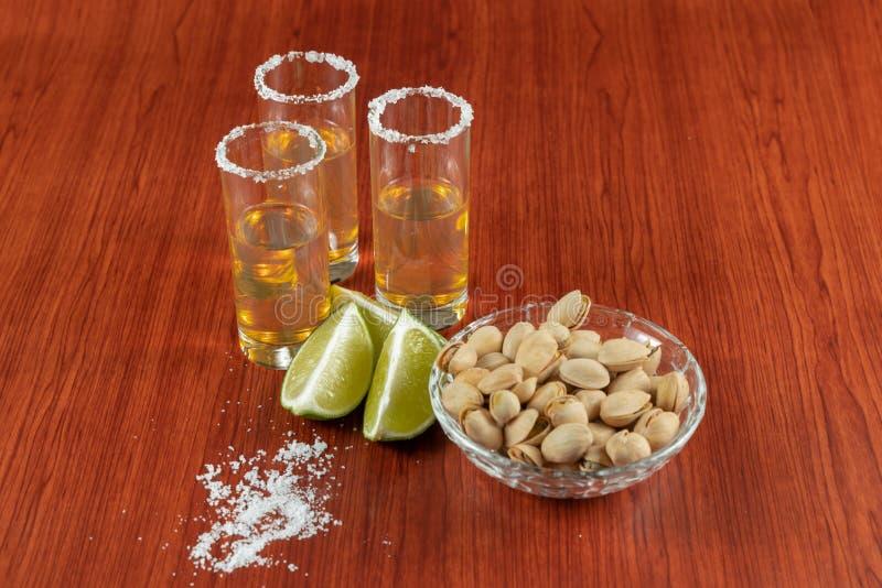 Tequila d'or avec le citron, les pistachos, le cacahuate, et le sel Boissons, boisson alcoolisée photos stock