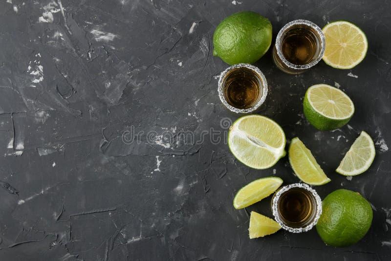 Tequila d'or dans un verre à liqueur en verre avec du sel et la chaux sur un fond concret noir Bar Boissons alcooliques Vue supér photographie stock