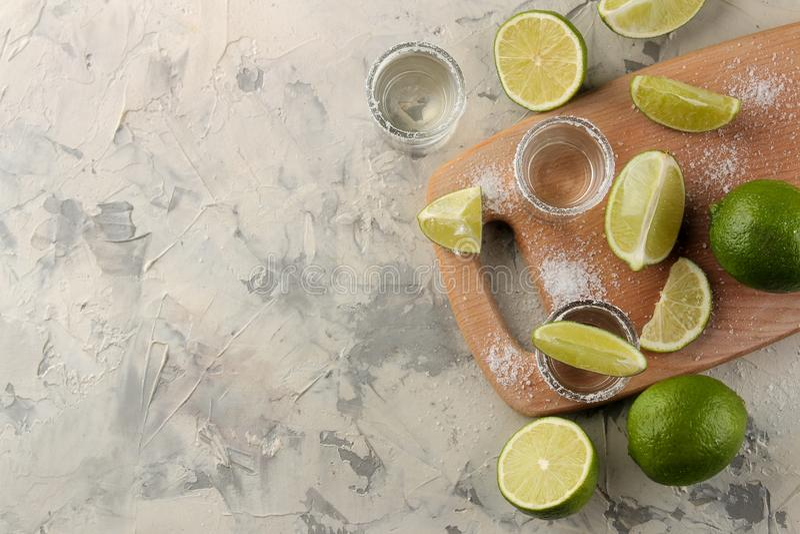 Tequila d'or dans un verre à liqueur en verre avec du sel et la chaux sur un fond de ciment Bar Boissons alcooliques Vue de ci-av photographie stock