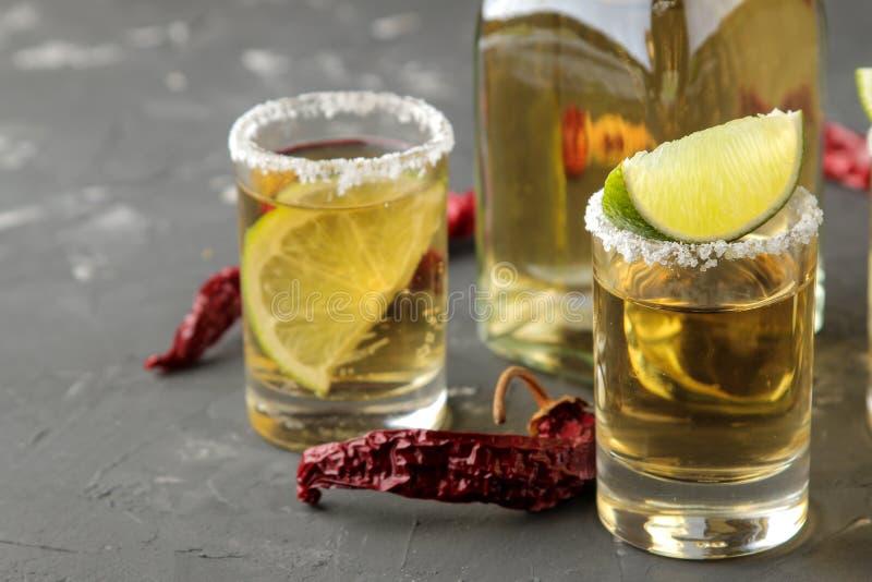 Tequila d'or dans un verre à liqueur en verre avec du sel, la chaux et le piment sur un fond concret noir Bar Boissons alcoolique photographie stock