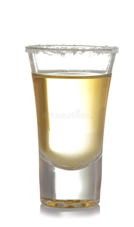 Tequila d'or dans un verre-verre avec la fin de sel sur un fond blanc d'isolement photographie stock