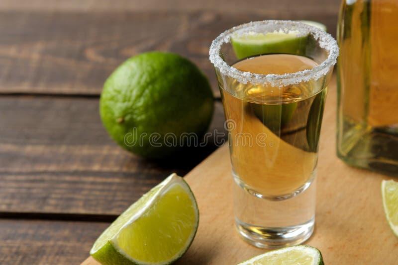 Tequila d'or dans verre-verre avec la fin de sel et de chaux sur le fond en bois brun image libre de droits