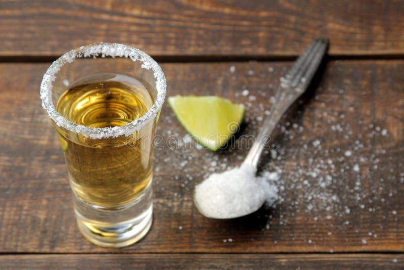Tequila de oro en el vidrio de cristal con cierre de la sal y de la cal para arriba en fondo de madera marrón foto de archivo