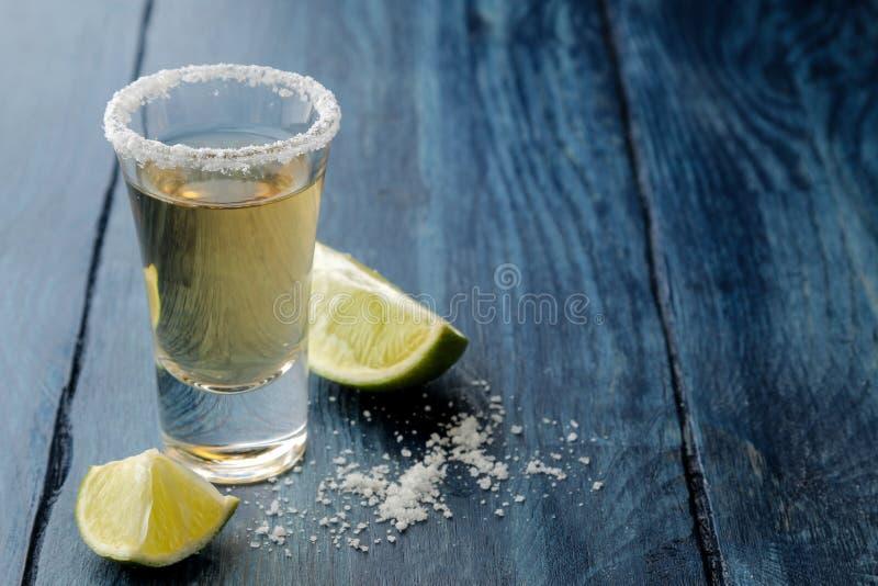 Tequila del oro en el vidrio de cristal con cierre de la sal y de la cal para arriba en fondo de madera azul Barra Bebidas alcohó imagen de archivo libre de regalías
