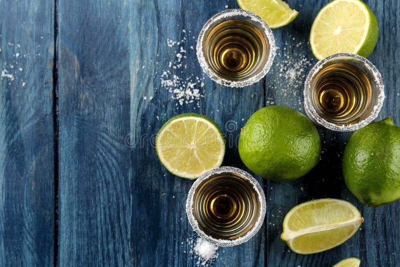 Tequila del oro en el vidrio de cristal con la sal y la cal en un fondo de madera azul Barra Bebidas alcohólicas Visión desde arr imágenes de archivo libres de regalías