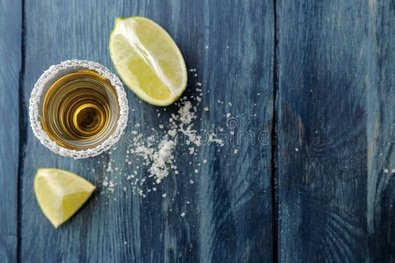 Tequila del oro en el vidrio de cristal con la sal y la cal en un fondo de madera azul Barra Bebidas alcohólicas Visión desde arr imagen de archivo libre de regalías