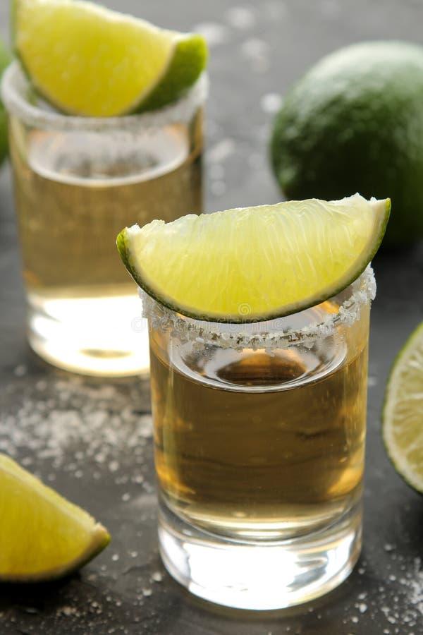 Tequila del oro en un vaso de medida de cristal con cierre de la sal y de la cal para arriba en un fondo concreto negro Barra Beb imagen de archivo libre de regalías