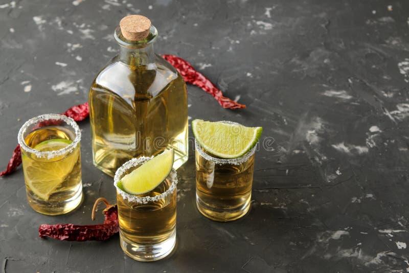 Tequila del oro en un vaso de medida de cristal con la sal, la cal y el pimiento picante en un fondo concreto negro Barra Bebidas fotos de archivo libres de regalías