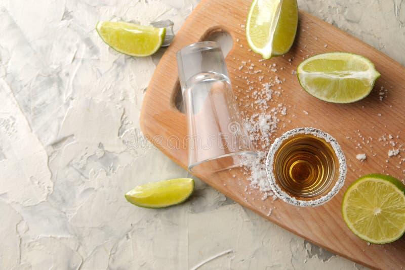 Tequila del oro en un vaso de medida de cristal con la sal y la cal en un fondo del cemento ligero Barra Bebidas alcohólicas Visi imagenes de archivo