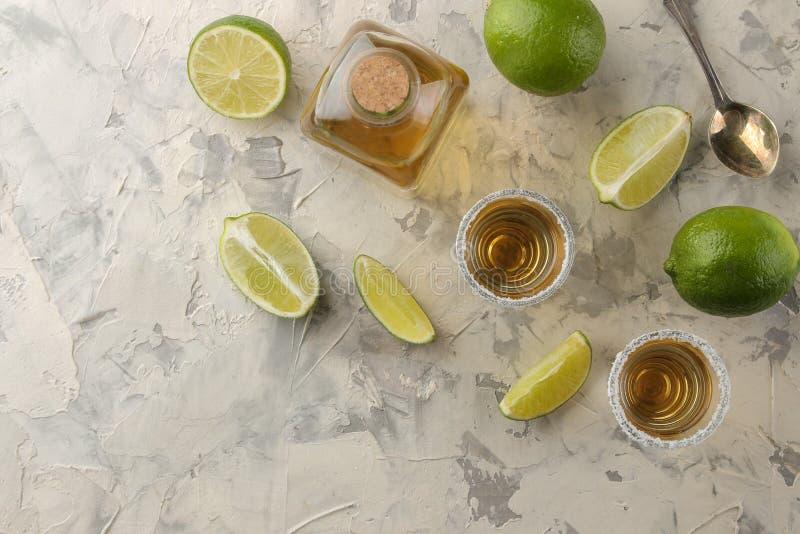 Tequila del oro en un vaso de medida de cristal con la sal y la cal en un fondo del cemento ligero Barra Bebidas alcohólicas Visi imagen de archivo libre de regalías