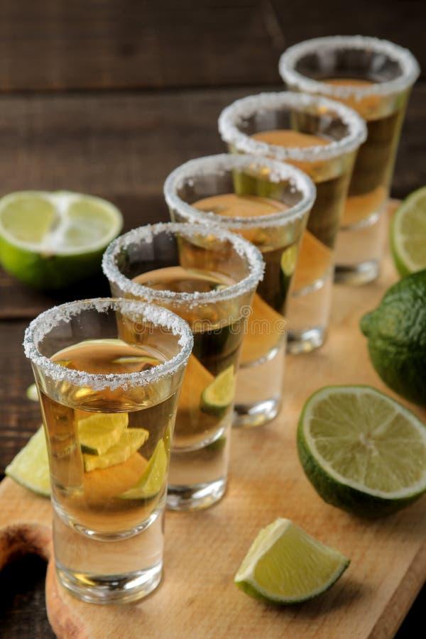 Tequila del oro en un vaso de medida de cristal con la sal y la cal en un fondo de madera marrón Barra Bebidas alcohólicas imagen de archivo