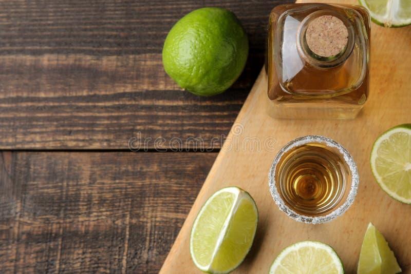 Tequila del oro en un vaso de medida de cristal con la sal y la cal en un fondo de madera marrón Visión superior con el espacio p imagenes de archivo