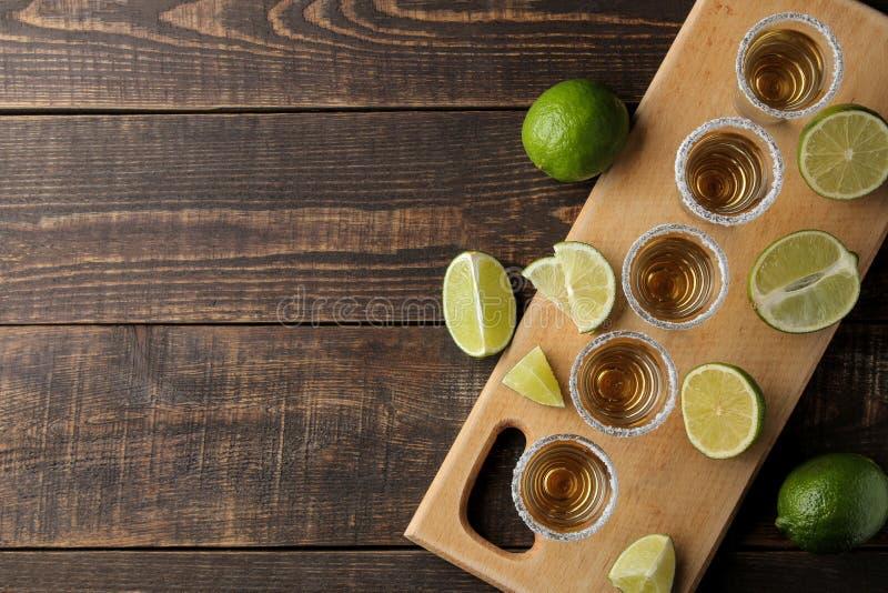Tequila del oro en un vaso de medida de cristal con la sal y la cal en un fondo de madera marrón Visión superior con el espacio p imagen de archivo libre de regalías