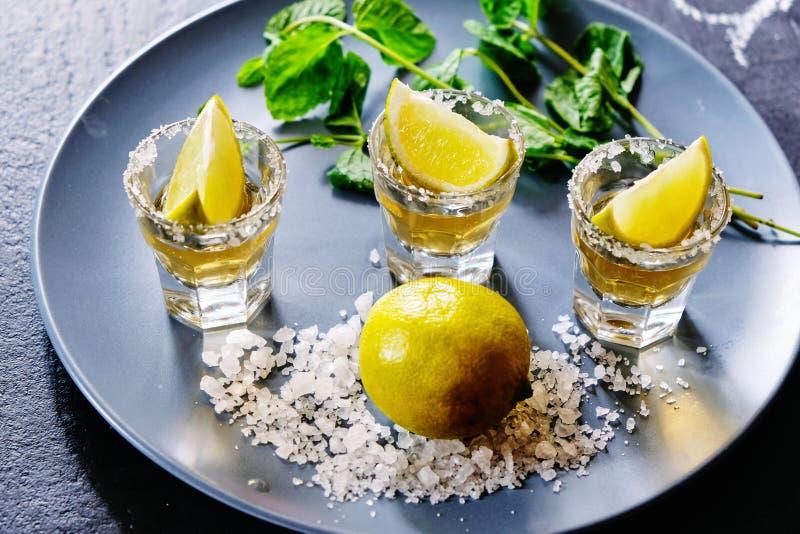 Tequila del oro tirado con la cal y la sal del mar en la placa gris fotografía de archivo libre de regalías