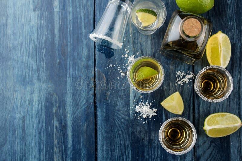 Tequila dell'oro in un vetro con sale e calce su una tavola di legno blu Bevande alcoliche Vista superiore fotografia stock libera da diritti