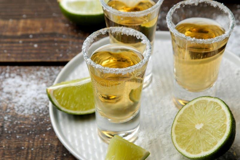 Tequila dell'oro in un vetro con sale e calce su una tavola di legno marrone Bevande alcoliche immagine stock libera da diritti