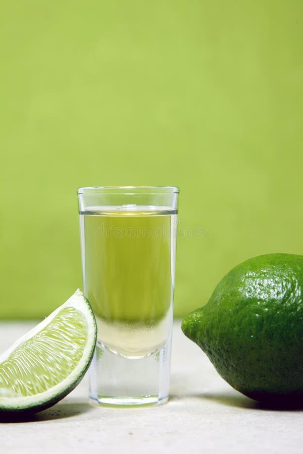 Tequila geschossen mit Kalk auf einem grünen Hintergrund stockbild