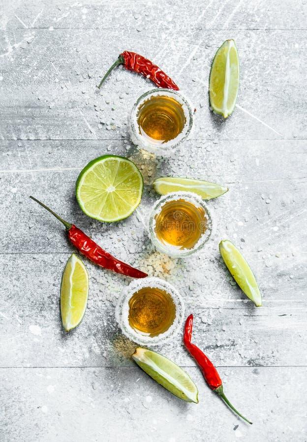 Tequila i ett skjutit exponeringsglas med skivor av limefrukt och glödhet peppar arkivbilder