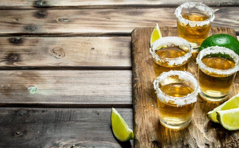 Tequila i ett skjutit exponeringsglas på en skärbräda med skivor av limefrukt fotografering för bildbyråer