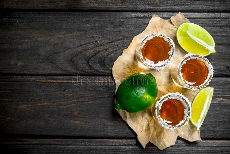 Tequila i ett skjutit exponeringsglas på papper med limefrukt royaltyfria bilder