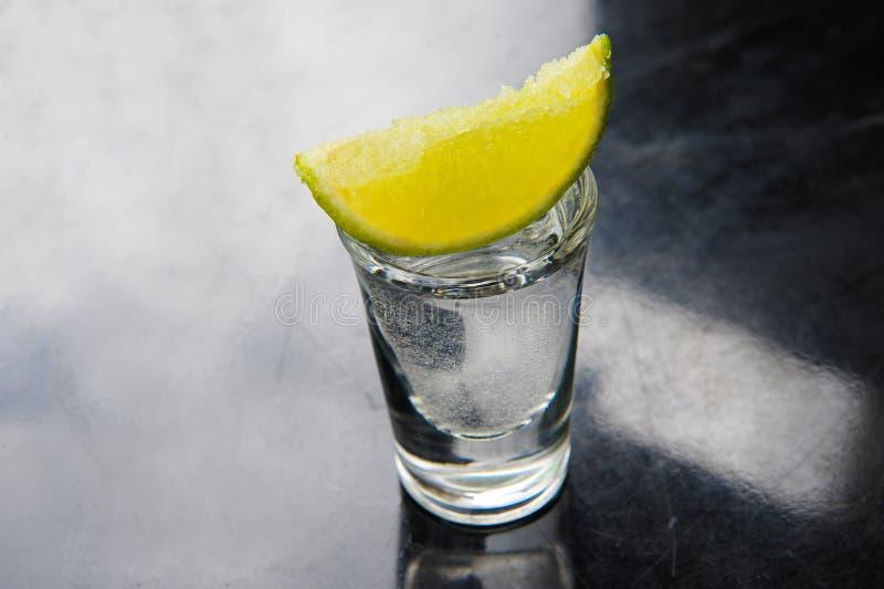 Tequila i skottexponeringsglas med limefrukt royaltyfri foto