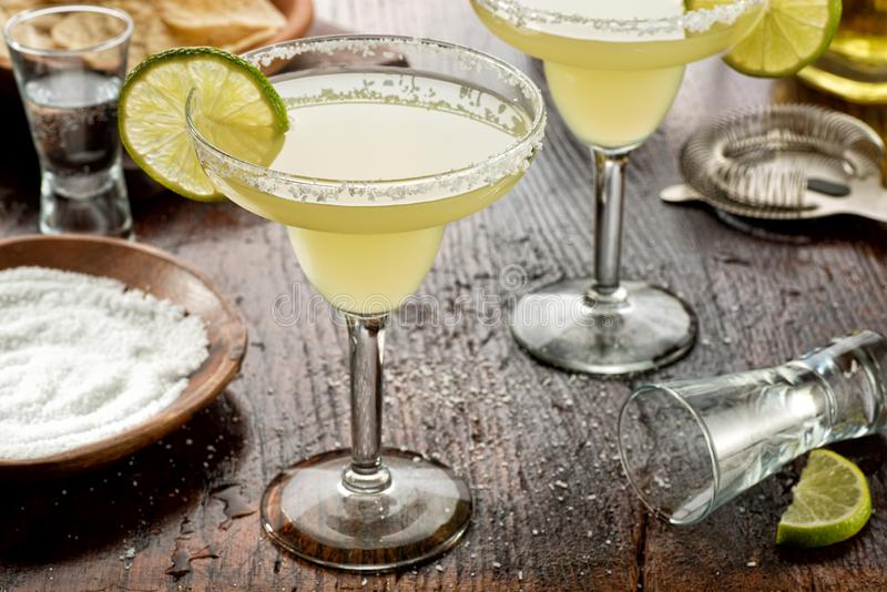 Tequila and Lime Margaritas. Delicious tequila and lime margaritas on a bar top with tortilla chips and pico de gallo stock image