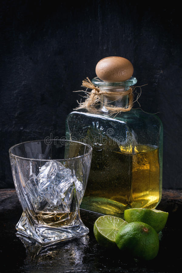 Tequila and limes. Glass of anejo tequila with ice cubes and bottle of tequila, served with sliced limes over black background royalty free stock photography