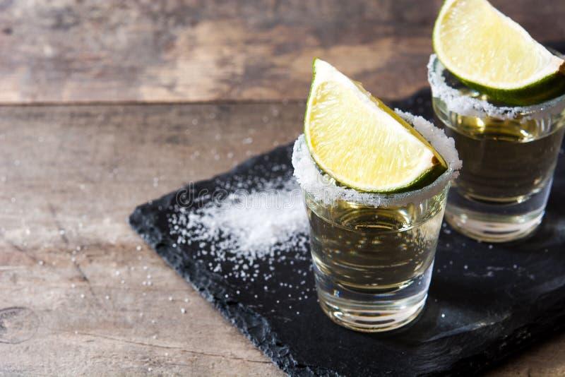 Tequila messicana dell'oro con calce e sale sulla tavola di legno fotografia stock
