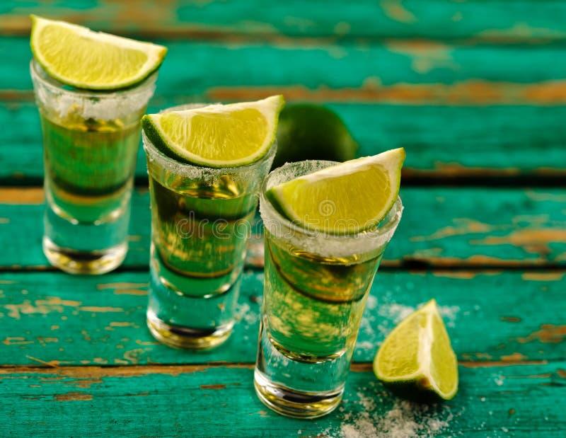 Tequila messicana dell'oro con calce e sale sulla tavola di legno immagini stock