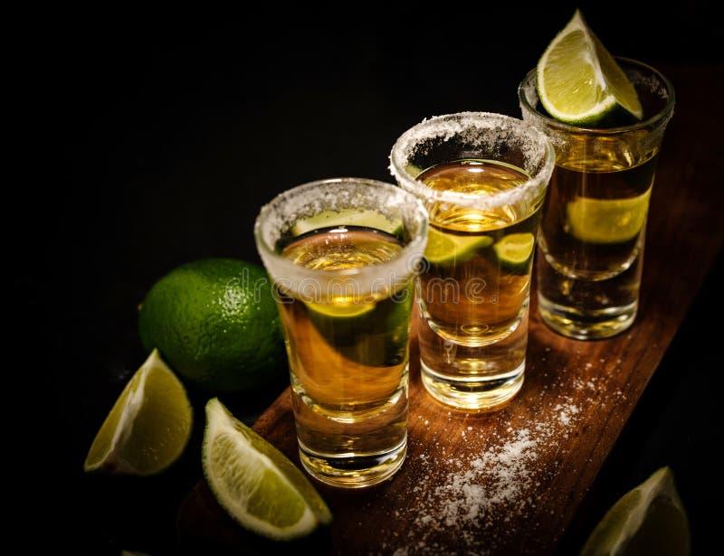 Tequila messicana dell'oro con calce e sale sulla tavola di legno fotografie stock libere da diritti
