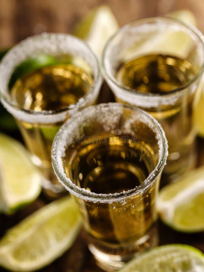 Tequila messicana dell'oro con calce e sale sulla tavola di legno immagine stock libera da diritti