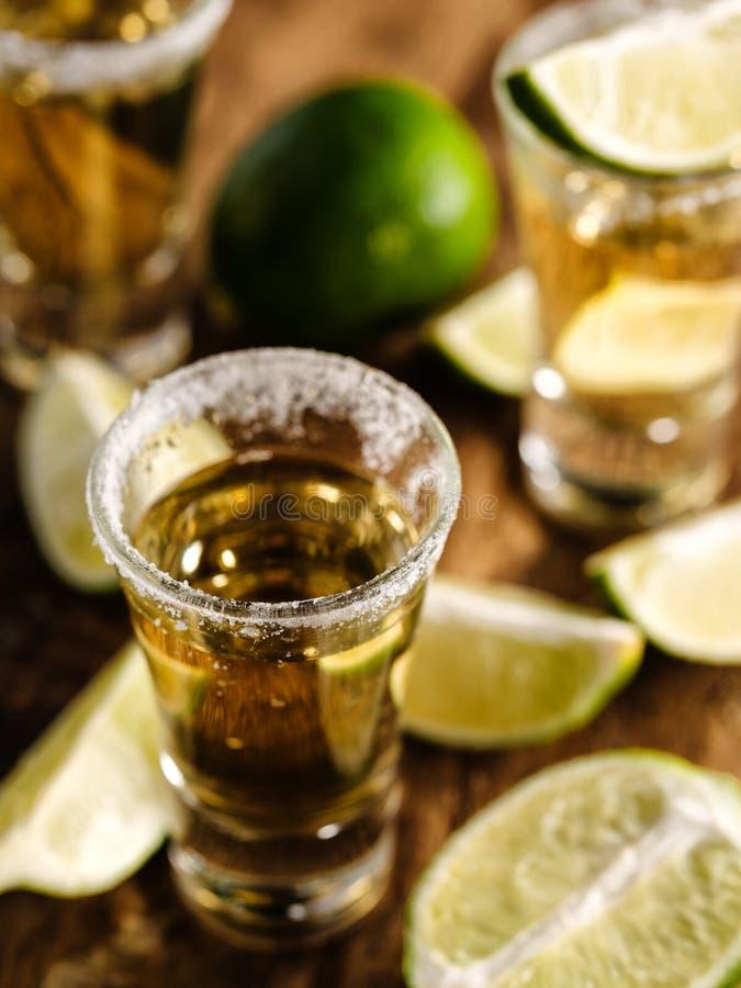 Tequila messicana dell'oro con calce e sale sulla tavola di legno fotografie stock