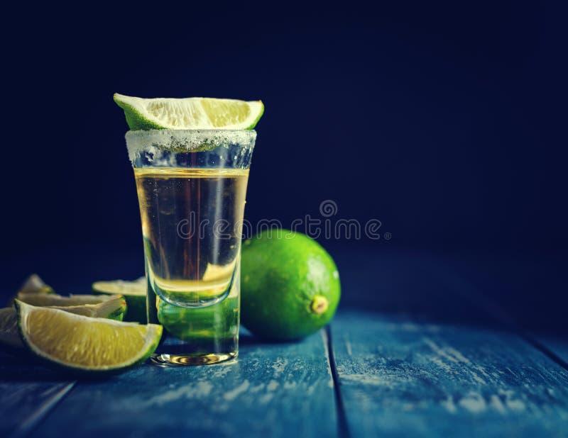 Tequila messicana dell'oro con calce e sale sulla tavola di legno immagine stock
