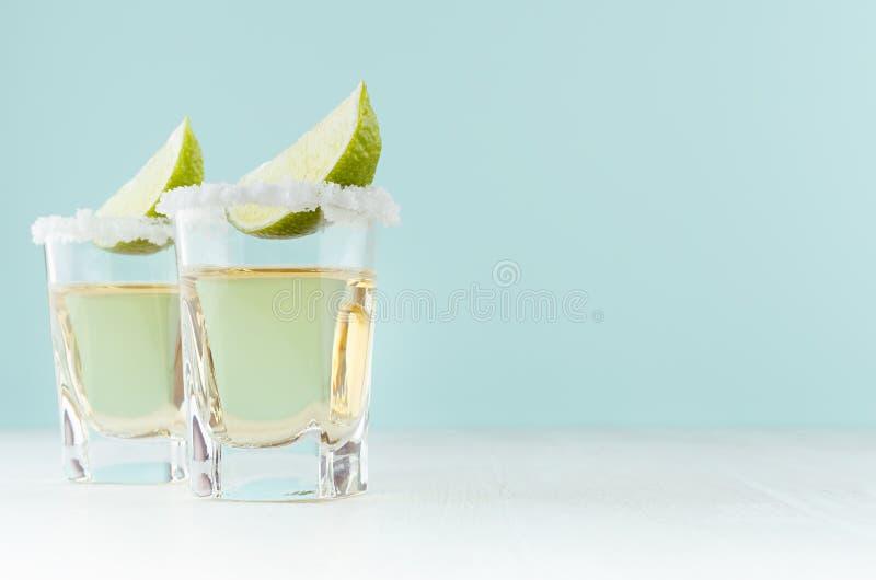 Tequila mexicano de oro de la bebida del alcohol con la cal de la rebanada, sal en el borde en bebida tirada en el fondo del colo foto de archivo libre de regalías